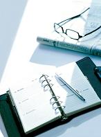 システム手帳とメガネと新聞