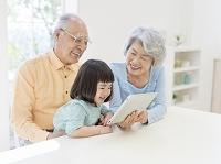 タブレットを見る祖父母と孫