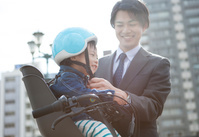 息子にヘルメットをかぶせる父親