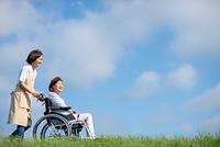 介護士に車椅子を押してもらうシニア女性