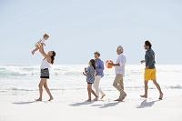 ビーチを歩く外国人の三世代家族