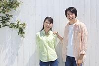 白い壁の前に並ぶ若いカップル