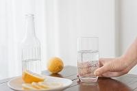 レモンと水の入ったコップを持つ手