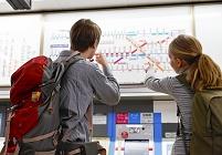 駅の路線案内を見る若い外国人カップル