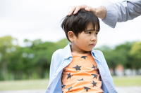 子供の頭を撫でる父親