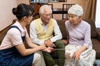 タブレットを見る日本人シニア夫婦とヘルパー