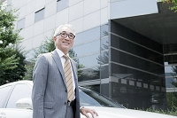 ビルの前に車を止めて立つ中高年日本人ビジネスマン