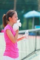 テニスコートで休憩する若い日本人女性
