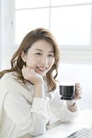 コーヒーカップを持つ笑顔のビジネスウーマン