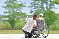 初夏のテラス・シニア女性と介護士さん