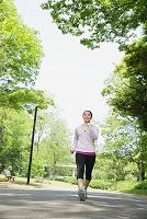 新緑の中でウォーキングをする女性