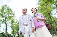 公園を歩くシニア夫婦