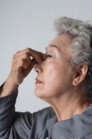 眉間を押さえるシニア日本人女性