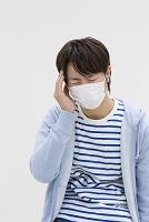 マスクをして頭に手をあてる若者日本人男性