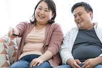 テレビを見る太ったカップル
