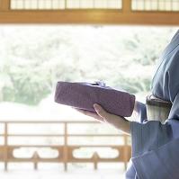 風呂敷包みを持った着物の女性