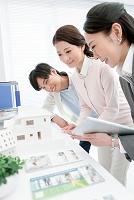 建築模型を見るビジネスウーマンと夫婦