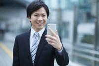 スマートフォンで写真を撮影する日本人ビジネスマン