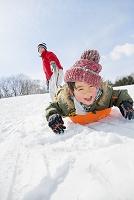 雪の公園でソリ遊びをする母と息子