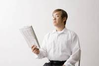 老眼で新聞を自分から離して読む中年男性
