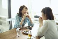 部屋で友人と話をする日本人女性