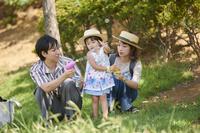 シャボン玉で遊ぶ三人家族