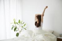 ベッドルームで起きて伸びをする日本人女性