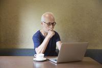 ノートPCで作業するシニアの日本人男性