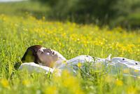 草原で寝転ぶ若い女性