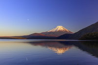 山梨県 本栖湖より夕日に染まる富士山と月