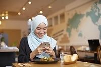 スマートフォンで撮影するムスリムの女性