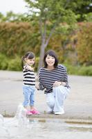 噴水で遊ぶ日本人親子