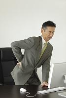 腰痛で顔をしかめる会社員