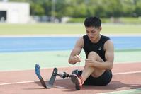靴ひもを結ぶ義足陸上競技選手