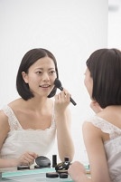 鏡の前で化粧する日本人女性