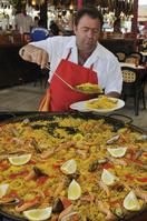 スペイン パエリアを盛り付ける店員