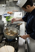 煮汁をかけながら魚を煮る調理師