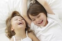 ベッドに寝転がる幼い兄妹