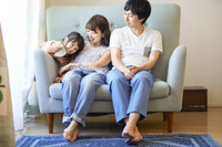 ソファでくつろぐ三人家族