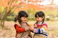 紅葉の公園で焼き芋を分けてあげる日本人の女の子