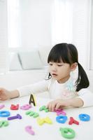 アルファベットのマグネットで遊ぶ女の子
