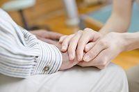 シニアの手を握る女性