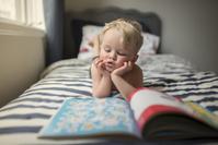 ベッドルームで本を読む白人の子供