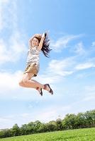 青空の下でジャンプする日本人女性