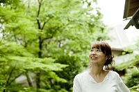 庭木を見上げる女性