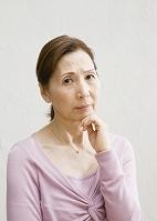 顎に手を当てるシニア日本人女性
