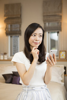 ベッドでスマートフォンを見る日本人女性