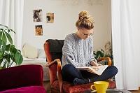 椅子に座ってノートを書く女性