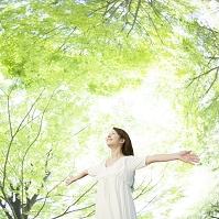 新緑の中で両手を広げる日本人女性