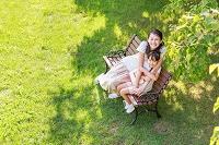 新緑の中、ベンチに座る仲の良い母子